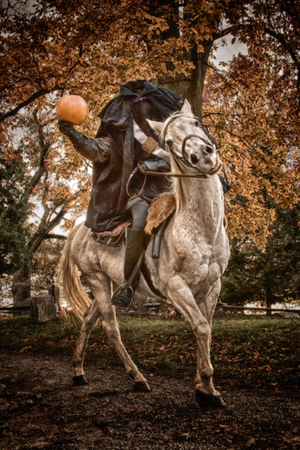 Headless horseman carrying pumpkin at Sleepy Hollow Cemetery.