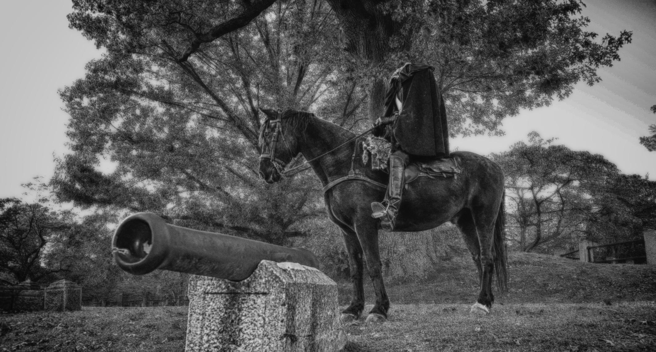 Headless horseman posed behind Sleepy Hollow Cemetery's Revolutionary War monument