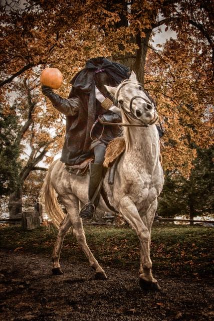 Headless horseman carrying pumpkin at Sleepy Hollow Cemetery.